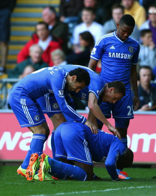 Demba Ba (ground) of Chelsea is congratulated by teammates after scoring the opening goal