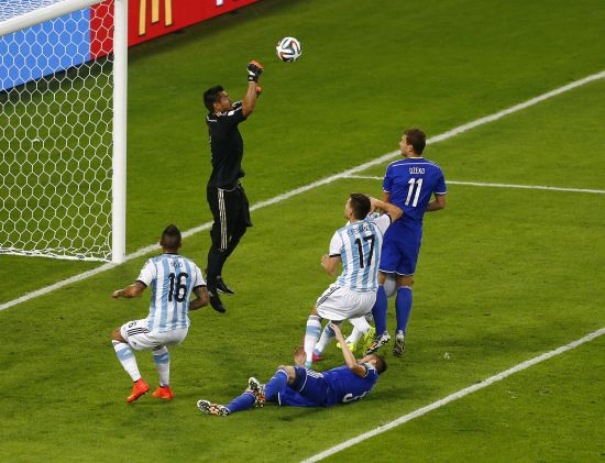 Argentina's goalkeeper Sergio Romero makes a save past Bosnia's Edin Dzeko (right)