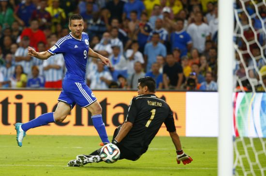 Bosnia's Vedad Ibisevic (L) scores through the legs of Argentina's Sergio Romero