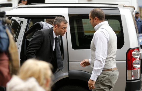 Olympic and Paralympic track star Oscar Pistorius (L) arrives ahead of his trial for the murder of his girlfriend Reeva Steenkamp