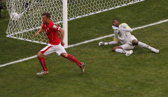Switzerland's Haris Seferovic (left) scores past Ecuador's Alexander Dominguez during their 2014 World Cup Group E match at the Brasilia national stadium