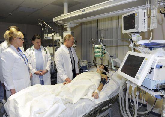Russia's President Vladimir Putin (R) visits Russian Olympic skicross racer Maria Komissarova at a hospital in Sochi,