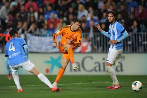 Cristiano Ronaldo (C) of Real Madrid shoots past Marcos Angeleri (R) and Flavio Ferreira of Malaga during the La Liga match