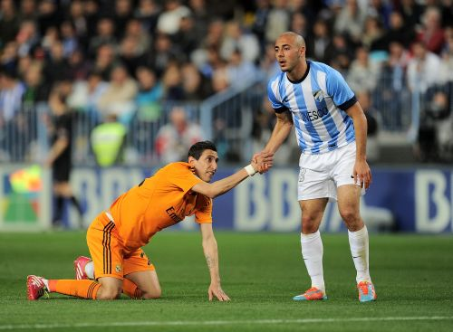 Nordin Amrabat (R) of Malaga gives a helping hand to Angel Di Maria of Real Madrid