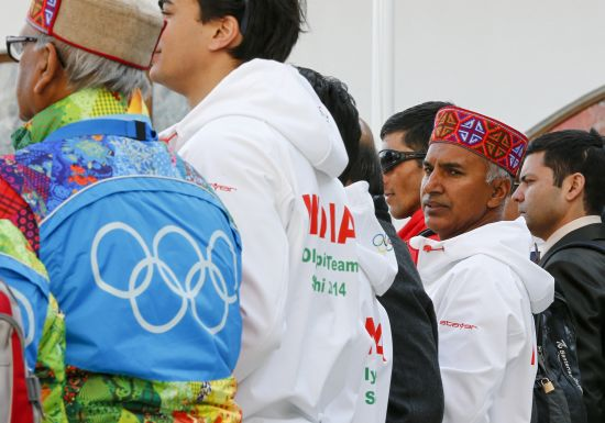 India's national team coach Roshan Lal Thakur (2nd R) looks back during the welcoming ceremony for the team in the Olympic athlete's village