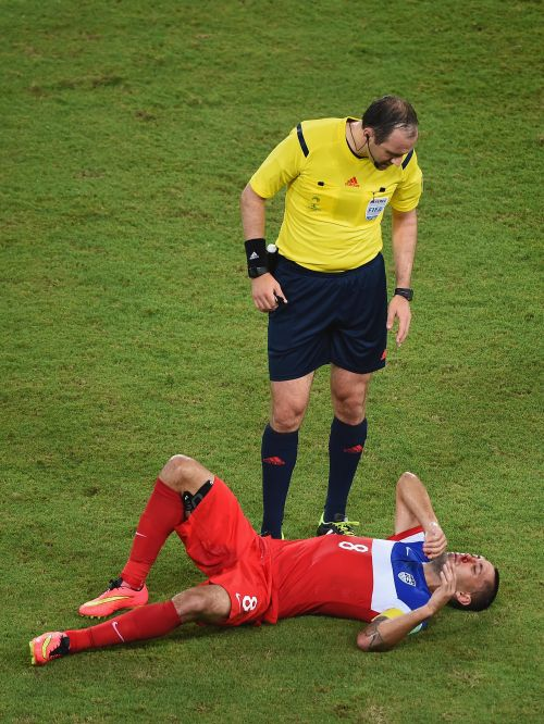 Clint Dempsey of the United States lies on the field as referee Jonas Eriksson stands over him