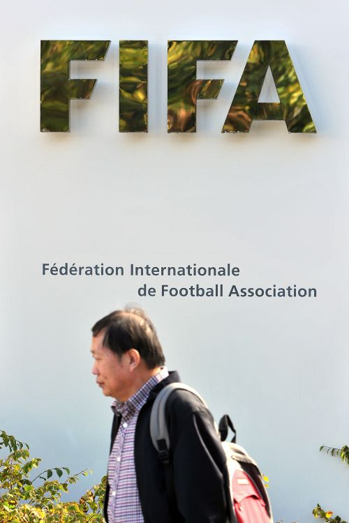 A man walks in front of the FIFA logo displayed outside the FIFA headquarters
