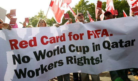 Members of the Swiss UNIA workers union display red cards and shout slogans during a protest in front of the headquarters of soccer's international governing body FIFA in Zurich