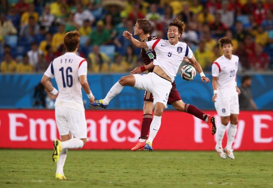 Kim Young-Gwon of South Korea and Alexander Kokorin of Russia jump for the ball