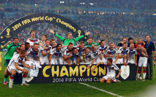 Germany's players pose for pictures as they celebrate with their World Cup trophy after winning their 2014 World Cup