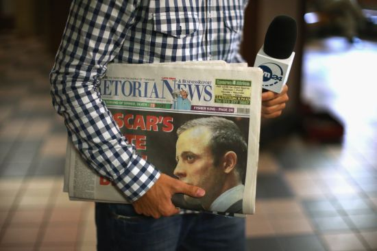 A television reporter holds a newpaper as he files a report from inside the foyer of North Gauteng High Court