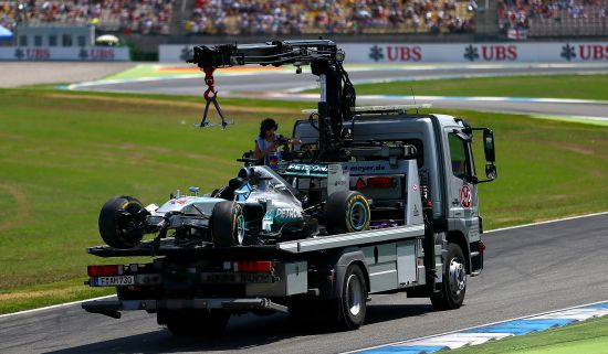 Lewis Hamilton of Great Britain and Mercedes GP's car is transported back to the team garage after crashing during qualifying ahead of the German Grand Prix