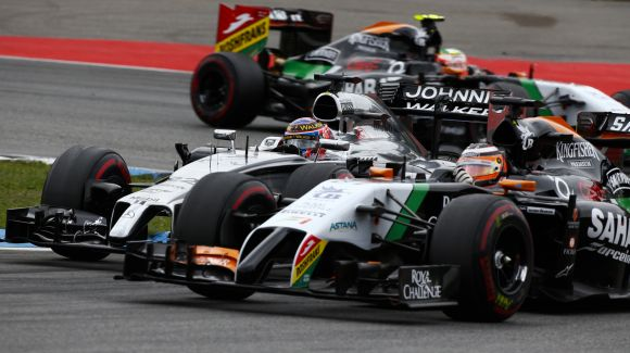 Force India Formula One driver Nico Hulkenberg of Germany (R) and McLaren Formula One driver Jenson Button of Britain (L) drive through a corner during the German F1 Grand Prix