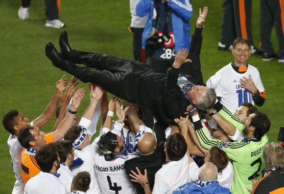 Real Madrid's coach Carlo Ancelotti is thrown in the air by his team as they celebrate after defeating Atletico Madrid.