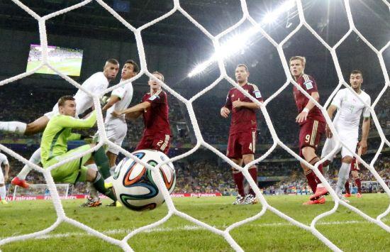 Algeria's Islam Slimani (2nd L) scores past Russia's goalkeeper Igor Akinfeev (L)