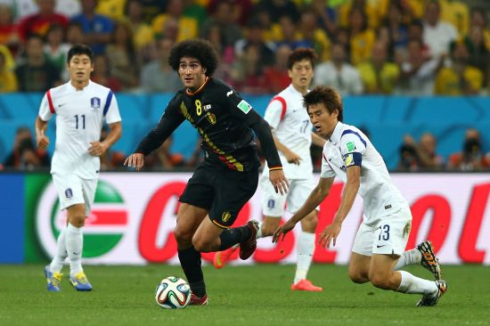 Marouane Fellaini of Belgium and Koo Ja-Cheol of South Korea compete for the ball