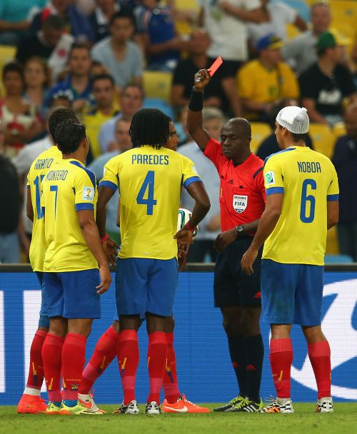 Antonio Valencia of Ecuador (obscured) is shown a red card by referee Noumandiez Doue
