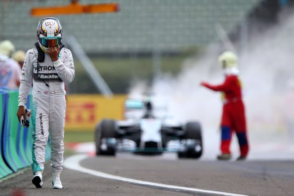 Lewis Hamilton of Great Britain and Mercedes GP walks away from his car after it caught fire during qualifying ahead of the Hungarian Formula One Grand Prix
