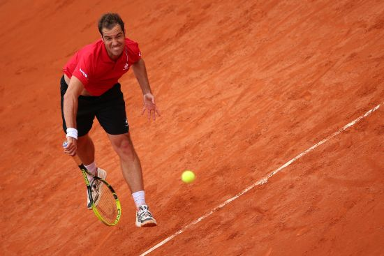 Richard Gasquet of France serves during his men's singles match against Bernard Tomic of Australia