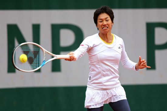 Kimiko Date-Krumm of Japan returns a shot during her women's singles match against Anastasia Pavlyuchenkova of Russia