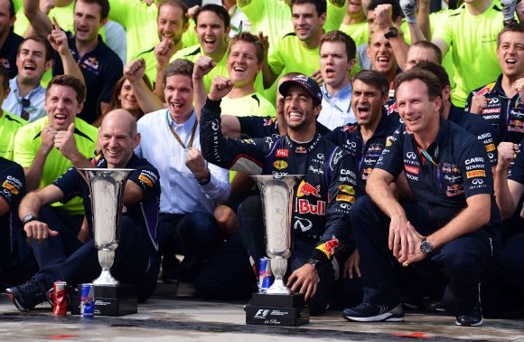 Daniel Ricciardo of Australia and Infiniti Red Bull Racing celebrates victory with the trophy and members of his team