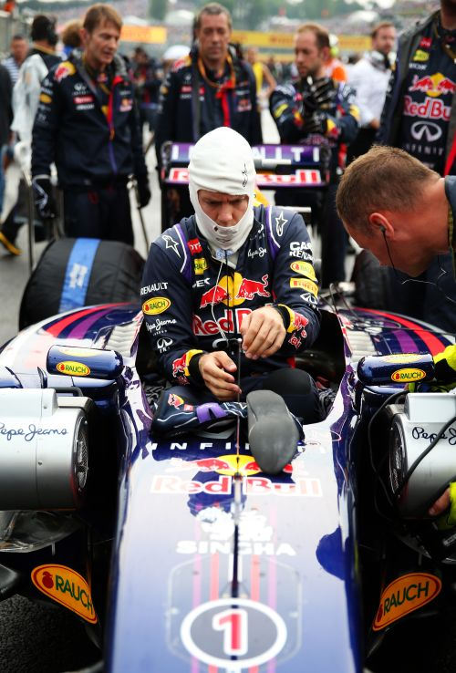 Sebastian Vettel of Germany and Infiniti Red Bull Racing gets into his car before the Hungarian Formula One Grand Prix