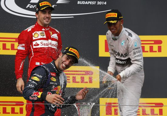 Winner Red Bull Formula One driver Daniel Ricciardo of Australia is splashed with champagne by second placed Ferrari Formula One driver Fernando Alonso of Spain (L) and third placed Mercedes Formula One driver Lewis Hamilton of Britain (R)