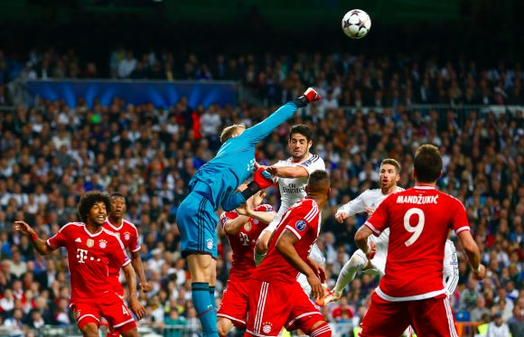 Bayern Munich's goalkeeper Manuel Neuer (C) saves a high ball