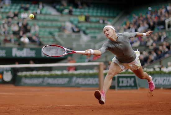 Anna Schmiedlova of Slovakia stretches to hit a return to Venus Williams.