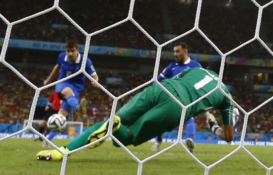 Greece's Sokratis Papastathopoulos (L) kicks to score a goal past Costa Rica's goalkeeper Keilor Navas