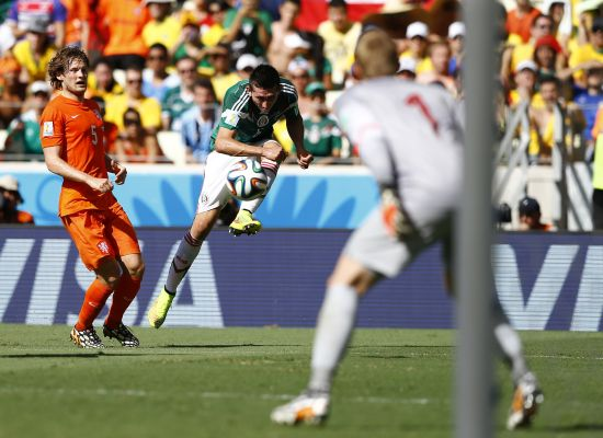 Mexico's Hector Herrera (C) tries to score past Daley Blind of the Netherlands