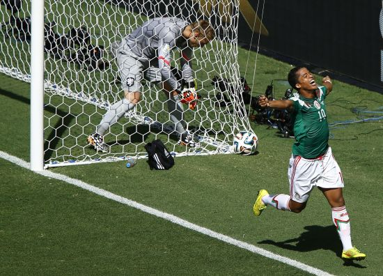 Jasper Cillessen of the Netherlands (L) picks the ball out of the net as Mexico's Giovani Dos Santos celebrates his goal