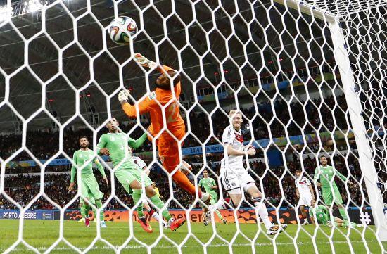 Germany's Andre Schuerrle (9) scores past Algeria's goalkeeper Rais Mbolhi