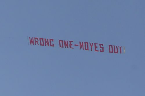 A plane flies overhead with a banner criticising Manchester United Manager David Moyes