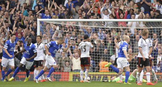Everton's players celebrate after Fulham's goalkeeper David Stockdale (lying on ground) scored an own goal