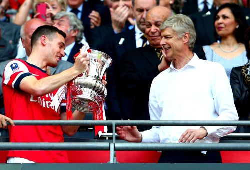 Captain Thomas Vermaelen of Arsenal passes the trophy to manager Arsene Wenger (right) after the FA Cup final against Hull City at Wembley Stadium on May 17, 2014.