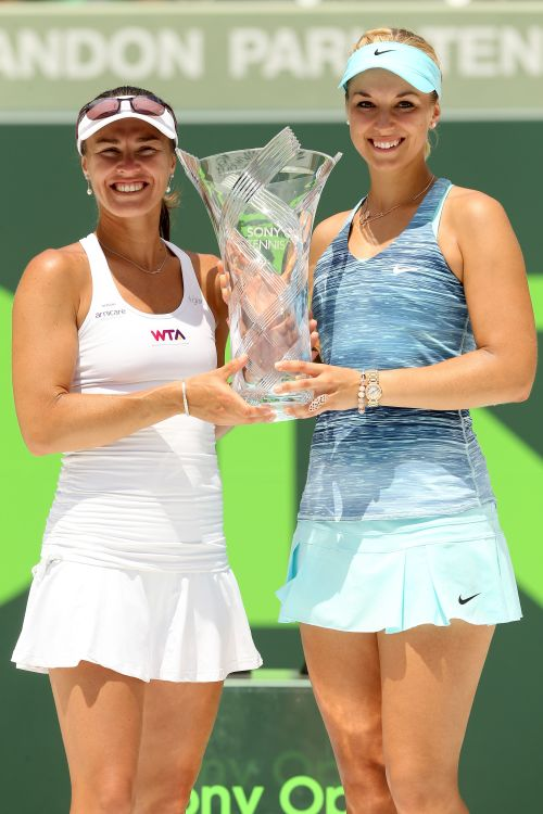 Martina Hingis of Switzerland and Sabine Lisiki of Germany pose for photographers with the Butch Buchholz Trophy