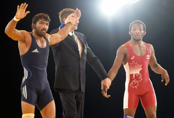Yogeshwar Dutt of India celebrates after beating Jevon Balfour of Canada