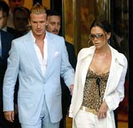 Real Madrid's new signing David Beckham (L) leaves his hotel with his wife Victoria in Madrid