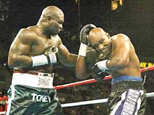 James Toney (L) connects on former heavyweight champion Evander Holyfield in the third round.