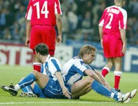 Porto's Edgaras Jankauskas (L) and Marco Ferreira sit on the pitch dejected after missing a goal
