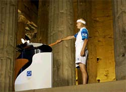 Greek Olympic medallist Niki Bakoyianni lights the Olympic torch in front of the columns of the Parthenon at the Acropolis