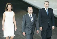 President of Greece Costis Stephanopoulos (C) walks with the President of the Athens 2004 Organising Committee Gianna Angelopoulos-Daskalaki (L) and IOC President Jacques Rogge of Belgium during the opening ceremony of the Athens 2004