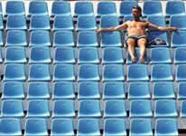 A lone spectator watches the men's singles first round Olympic tennis tournament match