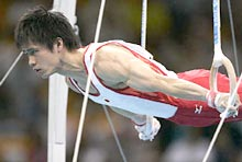 Japan's Hiroyuki Tomita performs a routine on the rings during the artistic gymnastics men's team final