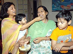 Dr Gayatri Rathore, wife of Rajyavardhan Singh Rathore, offering sweets to her mother-in-law and children at their residence in New Delhi