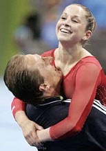 Carly Patterson (R) of the U.S. gets a hug from coach Yevgeny Marchenko after she clinched the gold medal in the women's artistic gymnastics individual all-round final