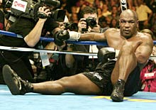 Mike Tyson sits on the canvas after being knocked out