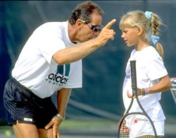 Tennis Coach Nick Bollettieri gives instructions to a young Anna Kournikova