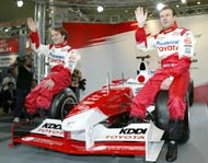 French Formula One driver Olivier Panis (R) and Brazilian Cristiano da Matta of Toyota wave to fans as they sit on Toyota's TF104 car for this season, during a Toyota Formula One fan-oriented event in Tokyo February 29, 2004.